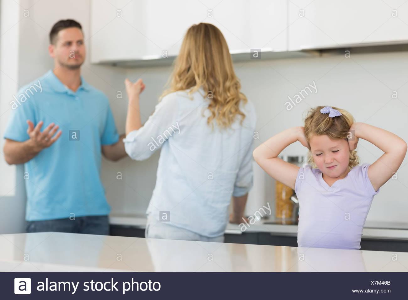 Chica que cubren las orejas mientras los padres argumentando Imagen De Stock