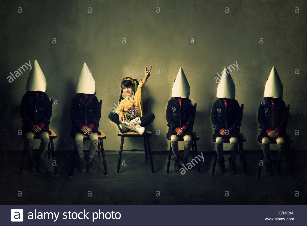 Seis niñas sentadas en sillas en una fila Imagen De Stock