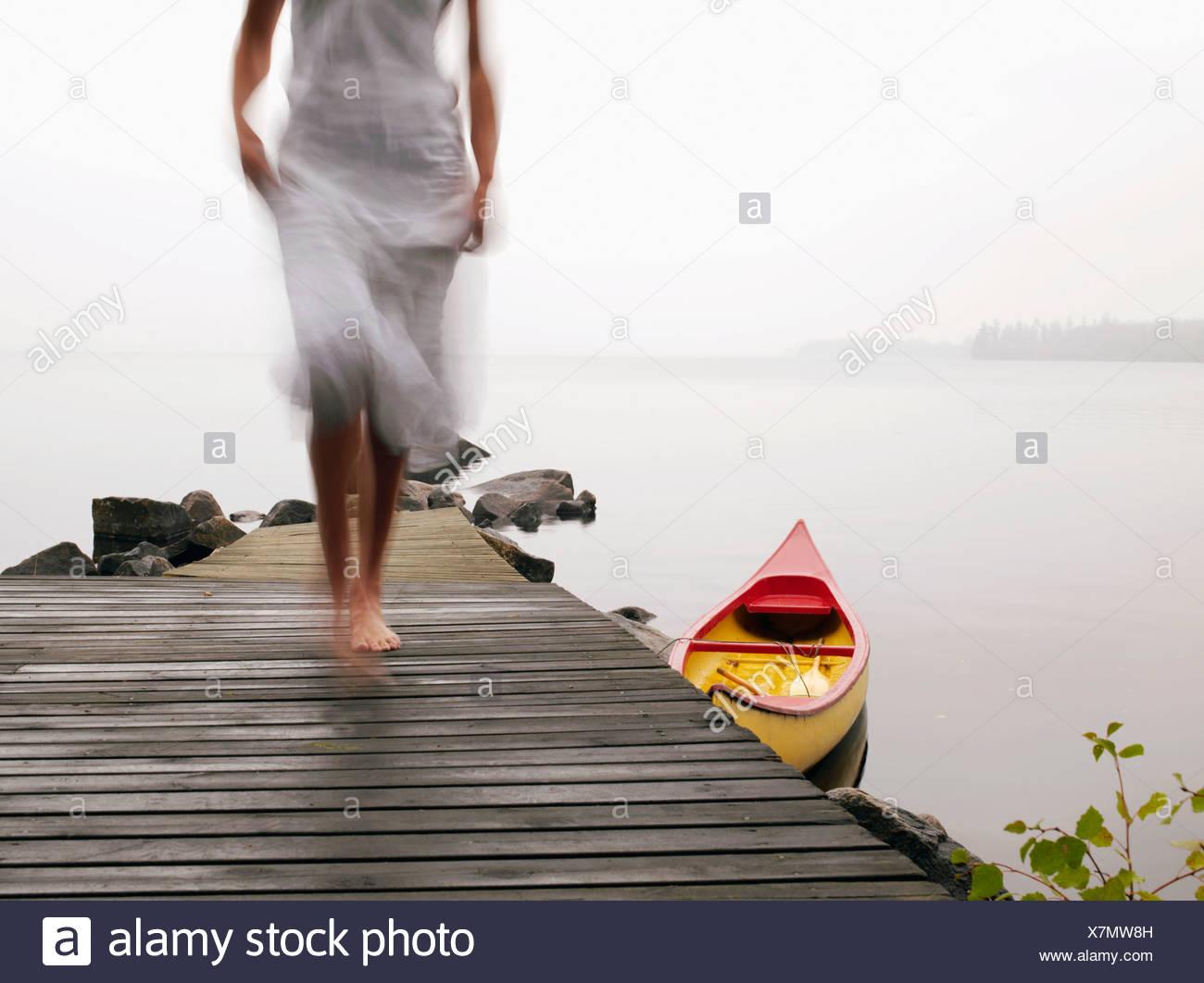 Mujer caminando sobre un muelle cerca de un barco. Imagen De Stock
