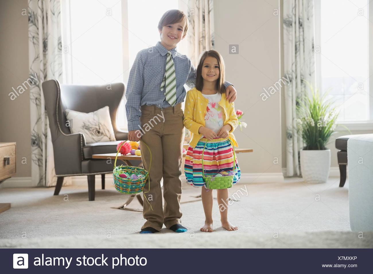 Retrato de hermanos llevando cestas de Pascua en casa Imagen De Stock