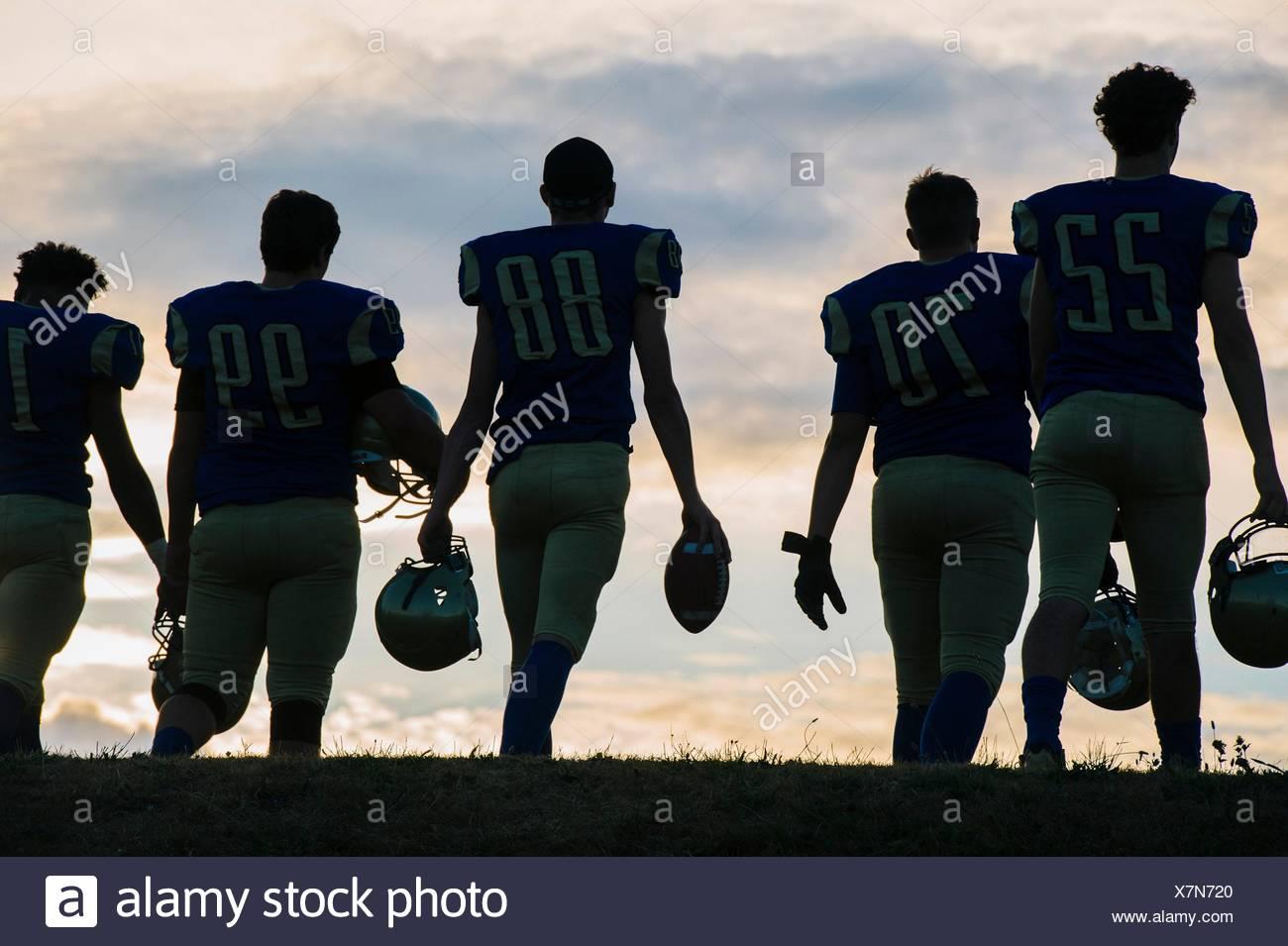 Grupo de jóvenes jugadores de fútbol americano a pie, vista trasera Imagen De Stock