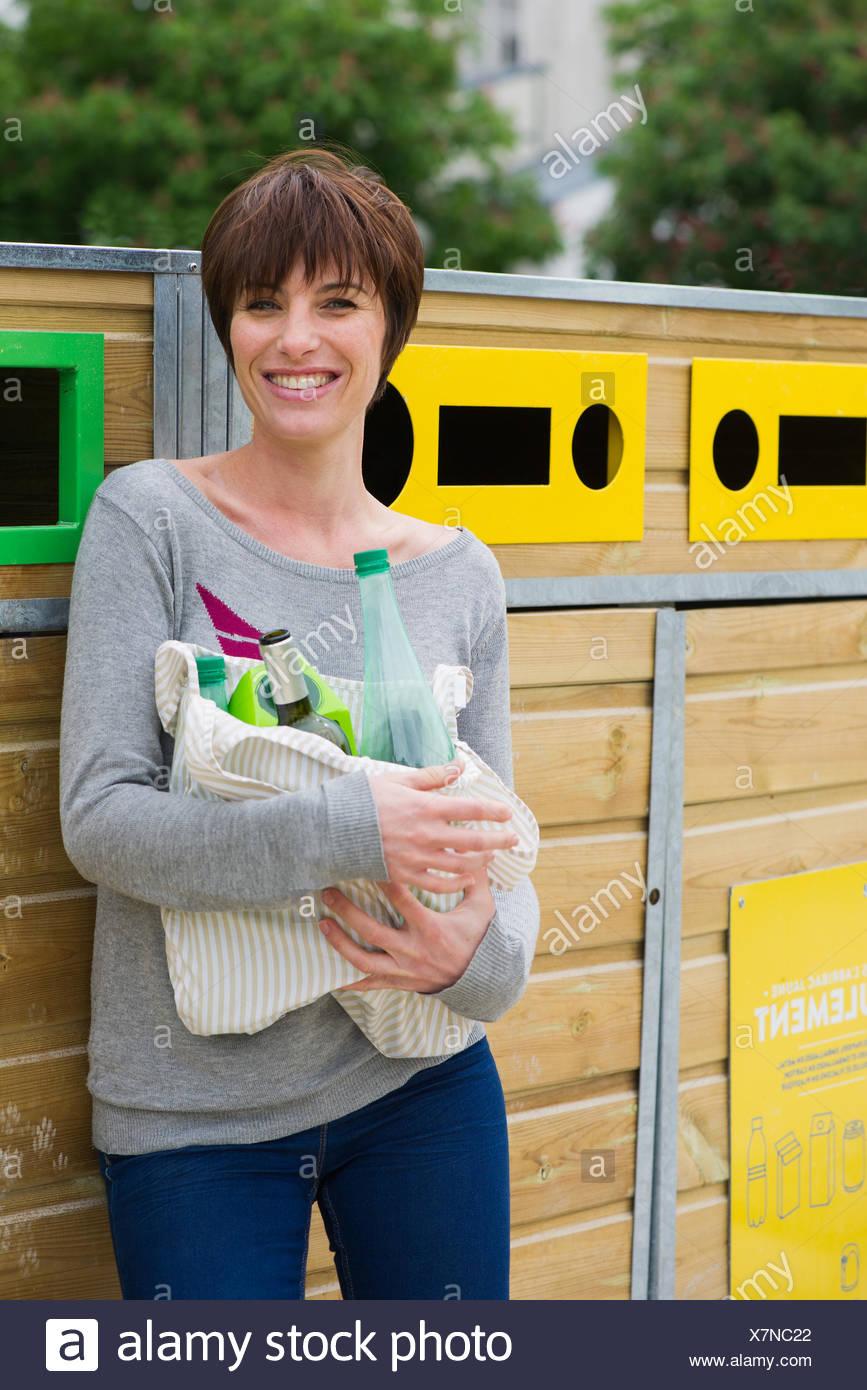 Mujer toma reciclables a la papelera de reciclaje Imagen De Stock