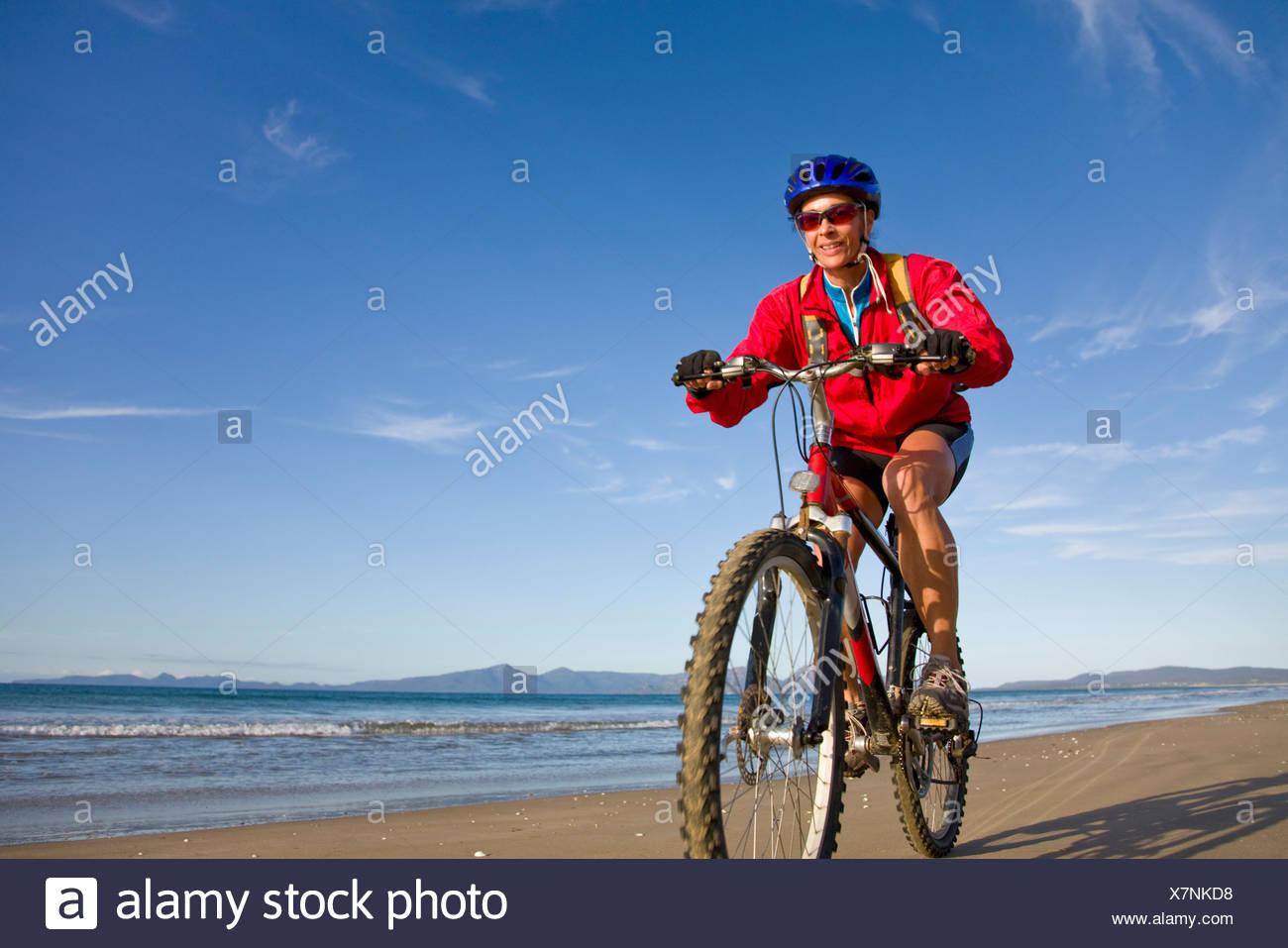 Una mujer disfrutando de un paseo en bicicleta en Nine Mile Beach, en la costa oriental de Tasmania, Australia. Foto de stock