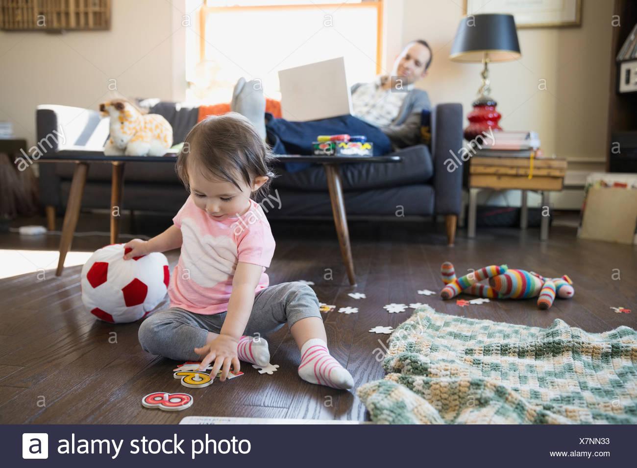 Padre con portátil viendo hija jugar Imagen De Stock