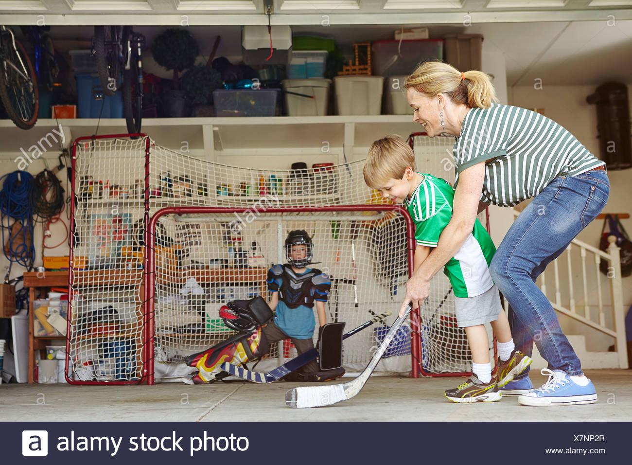 Madre jugando al hockey en garaje con dos hijos Imagen De Stock