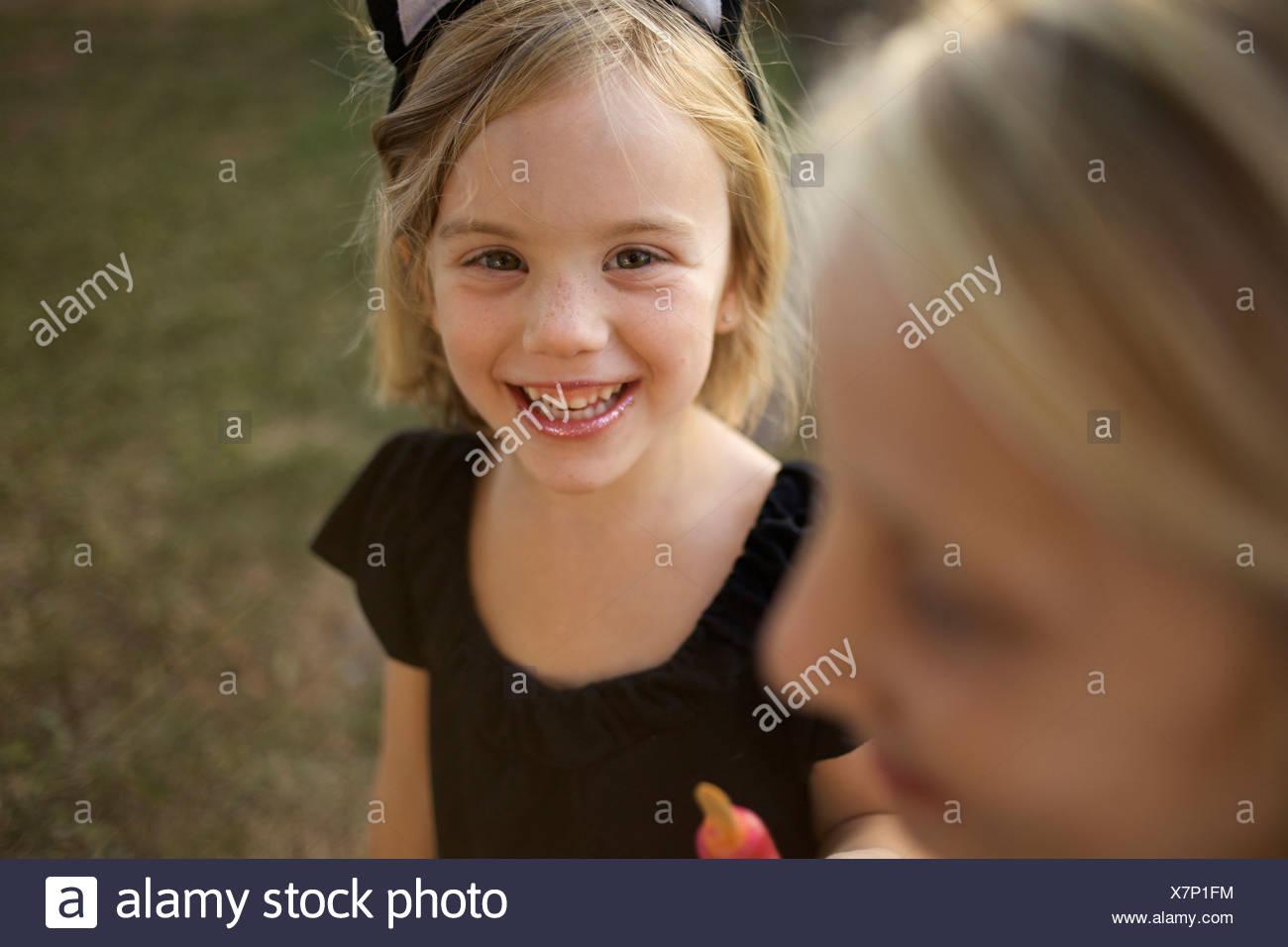 Chica sujetando su tratamiento en frío, vistiendo cat orejas, mira a la cámara y sonríe. Imagen De Stock