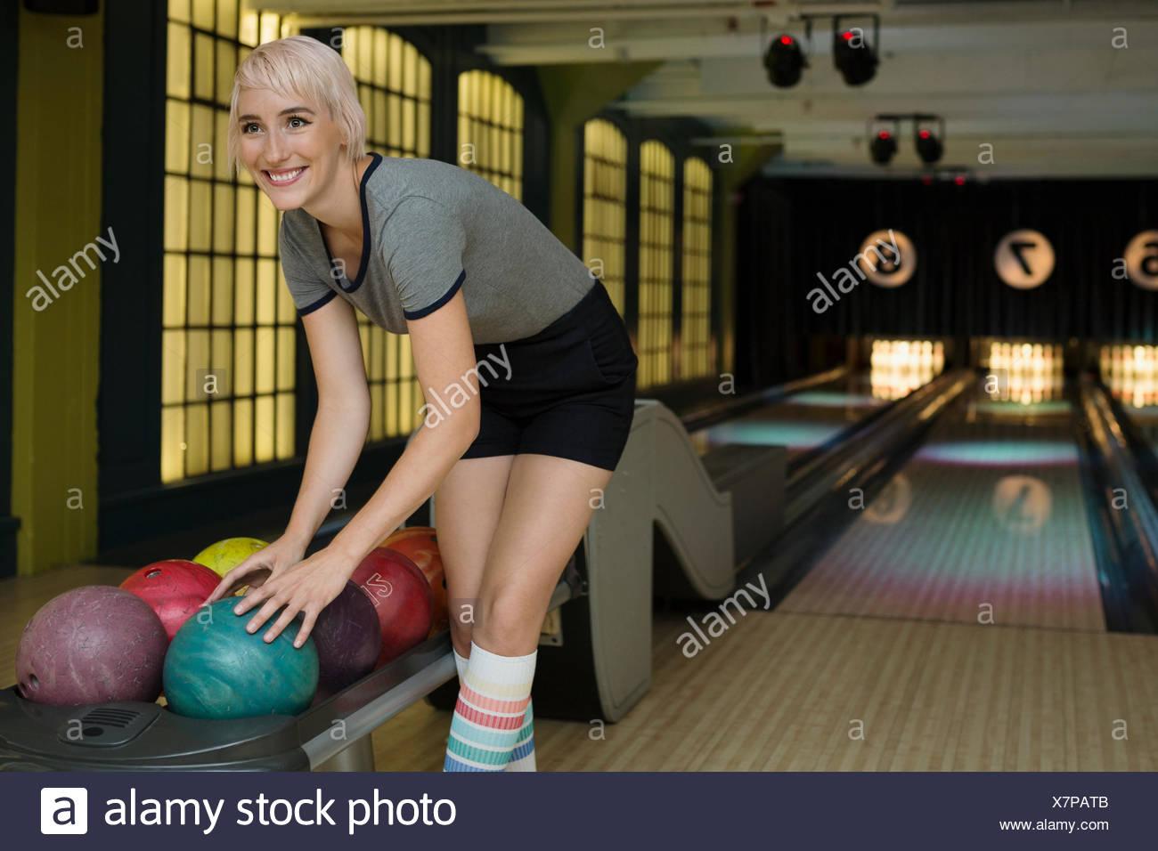 Mujer sonriente elegir bola de bolos de rack Imagen De Stock