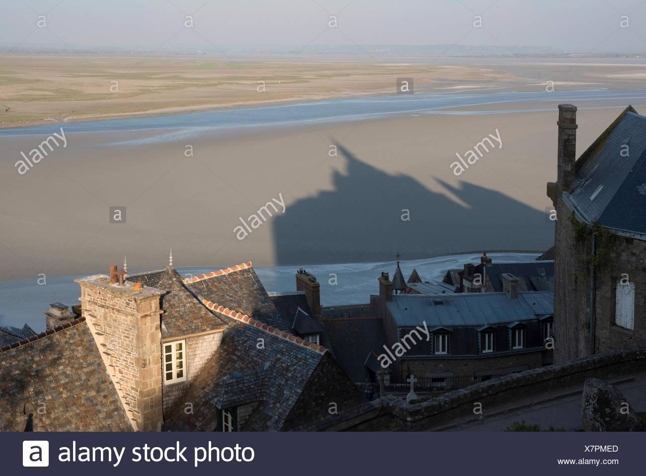 Los techos y sombra de Mont Saint-Michel, pisos de lodo en la marea baja, Baja Normandía, Francia, Europa Foto de stock