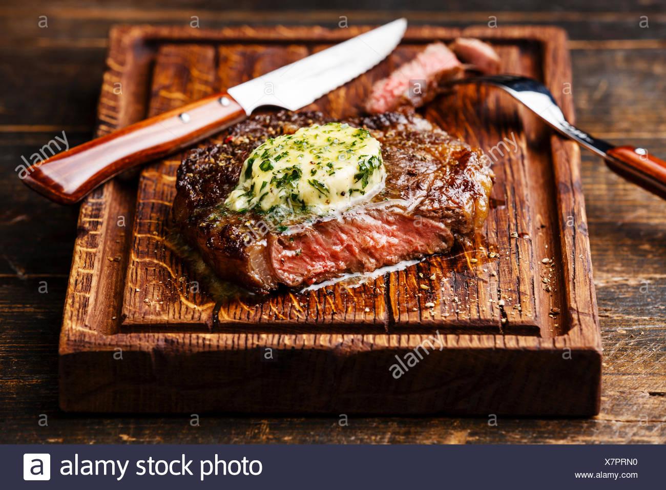 Medio raro el bistec a la parrilla chuletón con mantequilla de finas hierbas sobre placa de corte Imagen De Stock