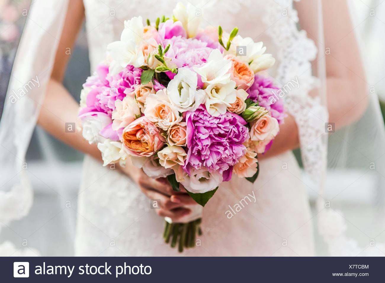 Sección media de la novia sosteniendo Bouquet Imagen De Stock