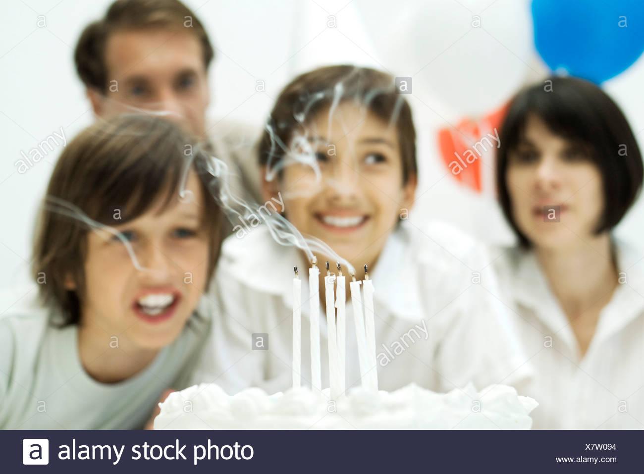 Los niños soplar las velas en el pastel de cumpleaños, los padres en segundo plano. Foto de stock