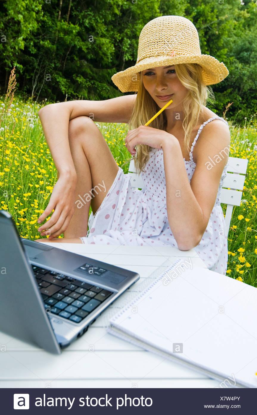 Adolescente en hat utilizando el portátil en el florido prado Imagen De Stock