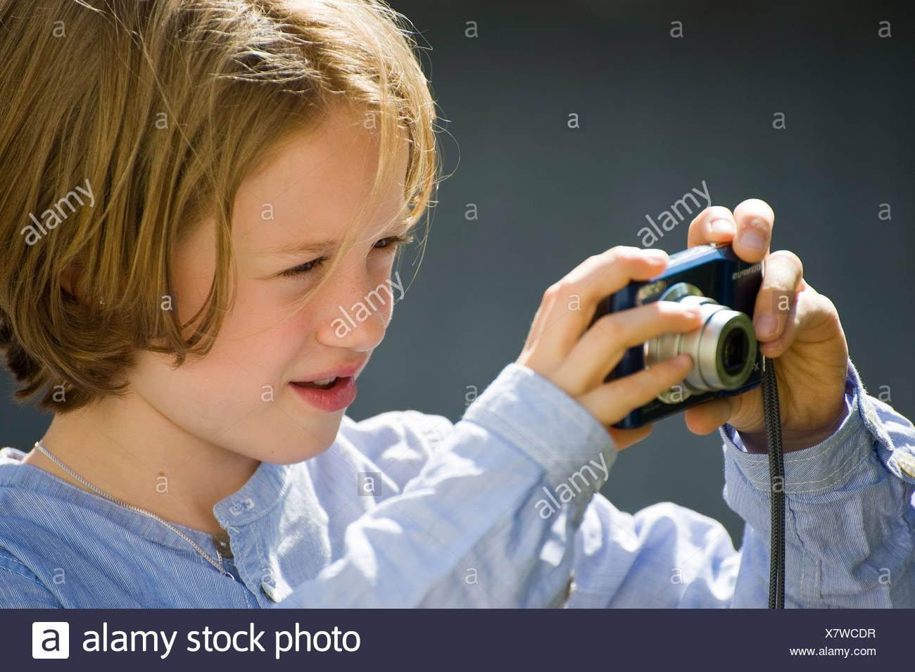 Niña de ocho años, tomar fotografías con una cámara digital. Imagen De Stock