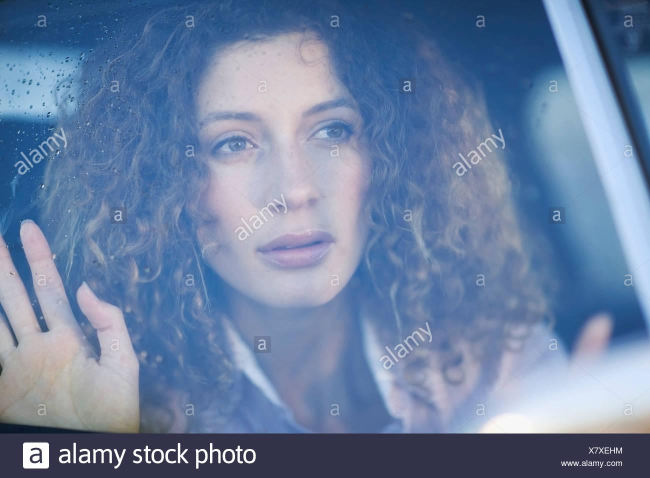 Mujer mirando por la ventanilla de un coche Imagen De Stock