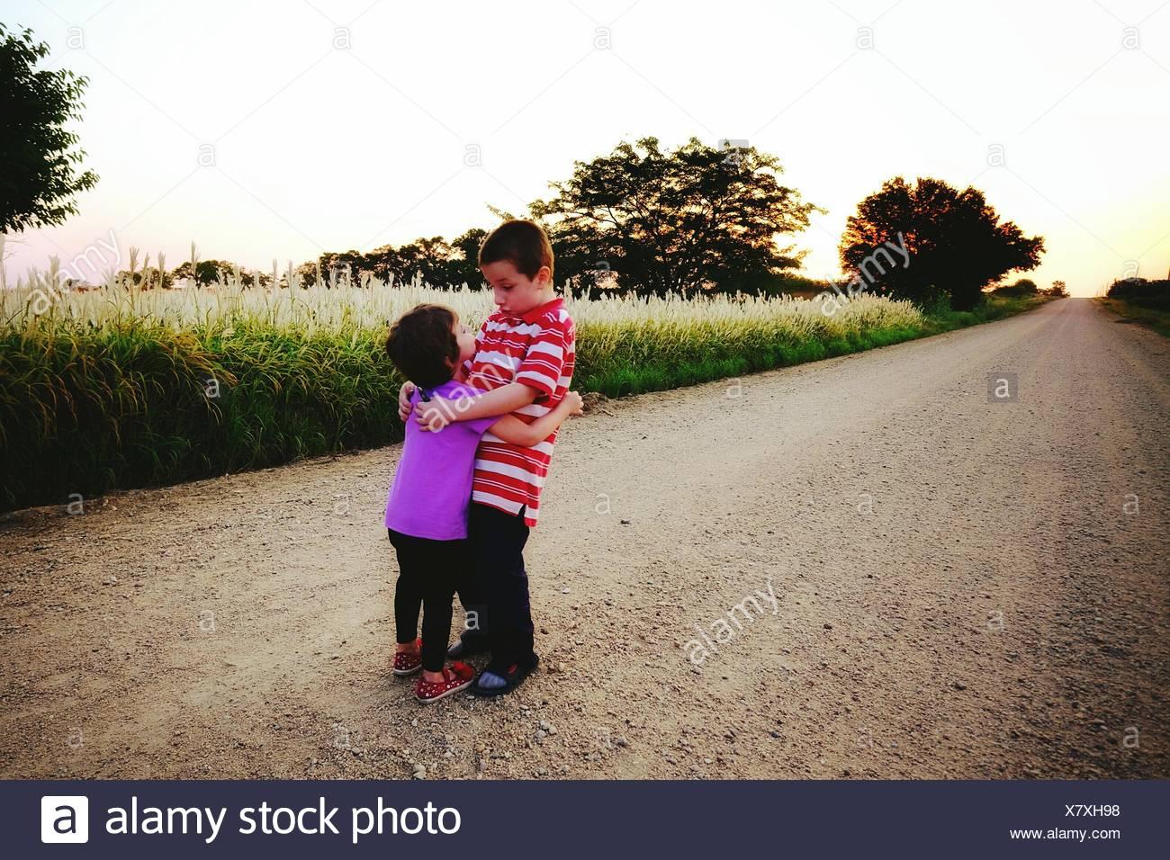 Hermano y hermana dando un abrazo en la carretera de Campo Imagen De Stock
