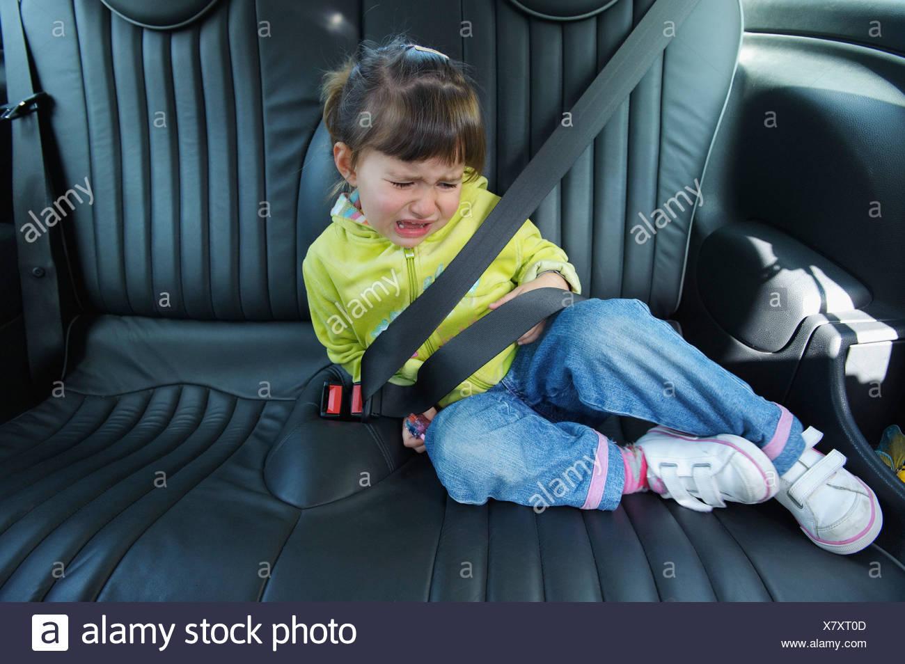 Cádiz, España; una joven llora mientras está sentada en un vehículo con el cinturón abrochado Foto de stock