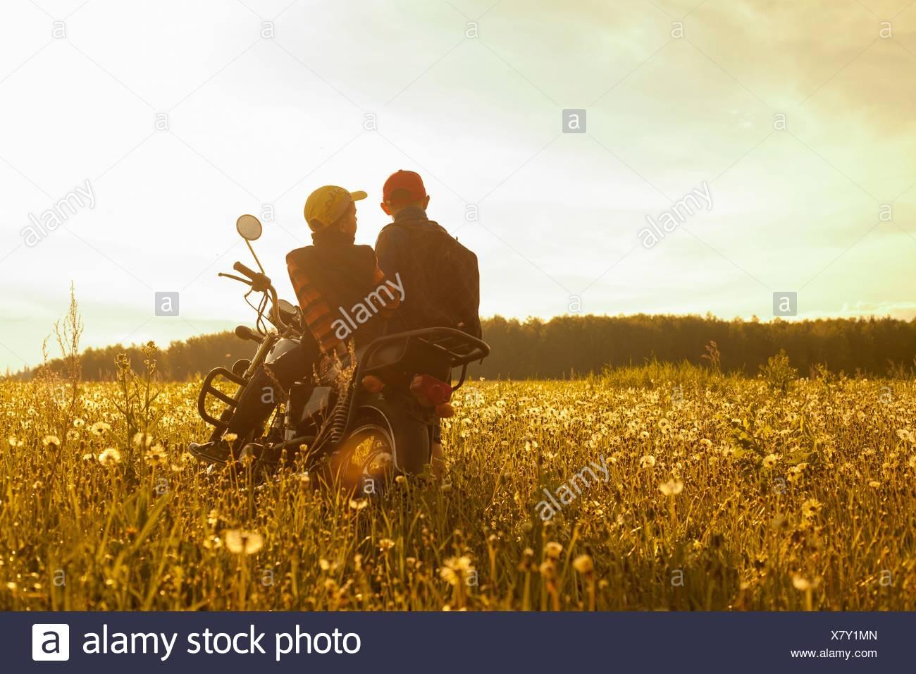 Dos chicos, sentado en una motocicleta, en el campo, vista trasera Imagen De Stock