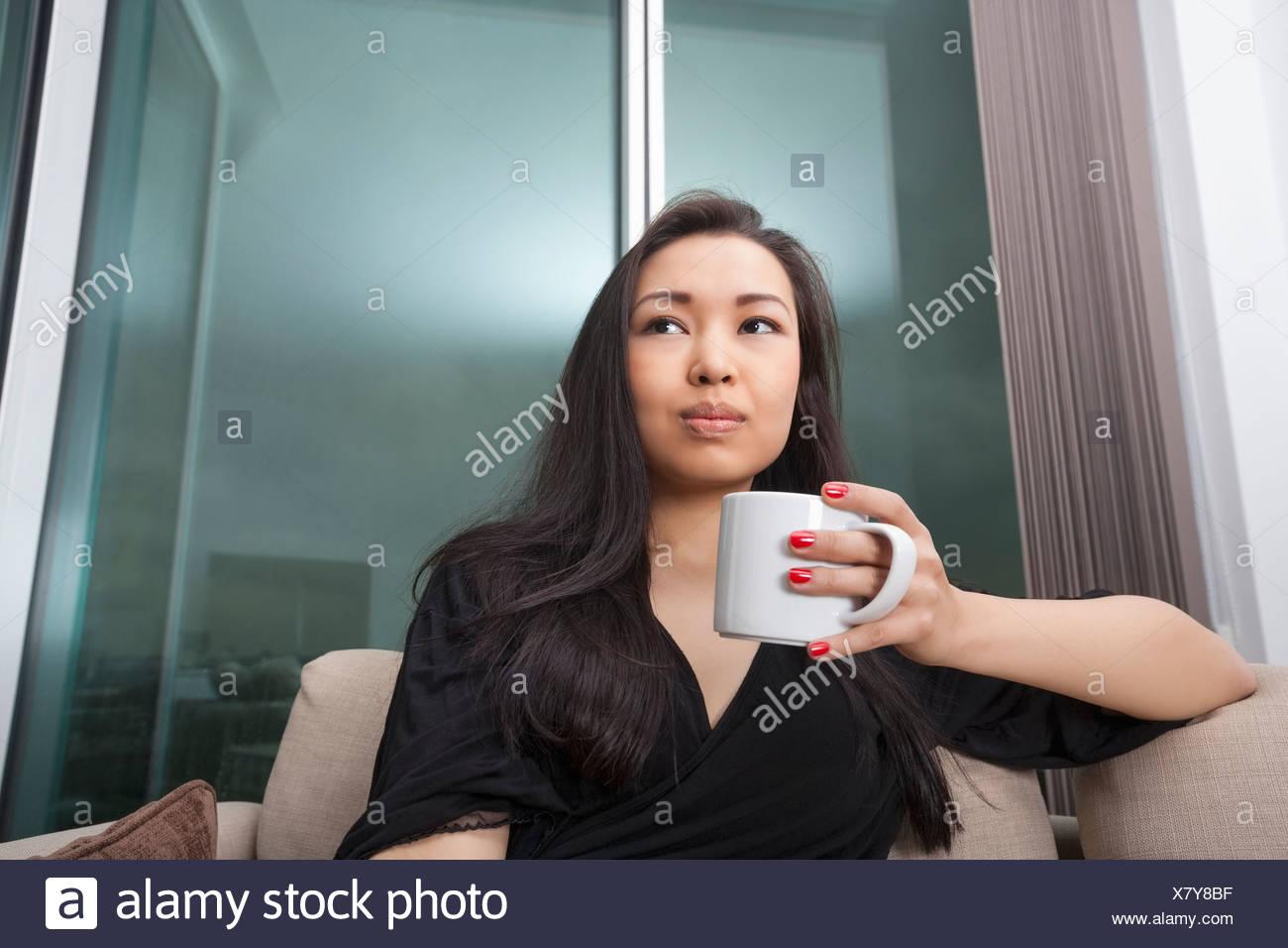 Pensativo joven tomando café en el salón Imagen De Stock