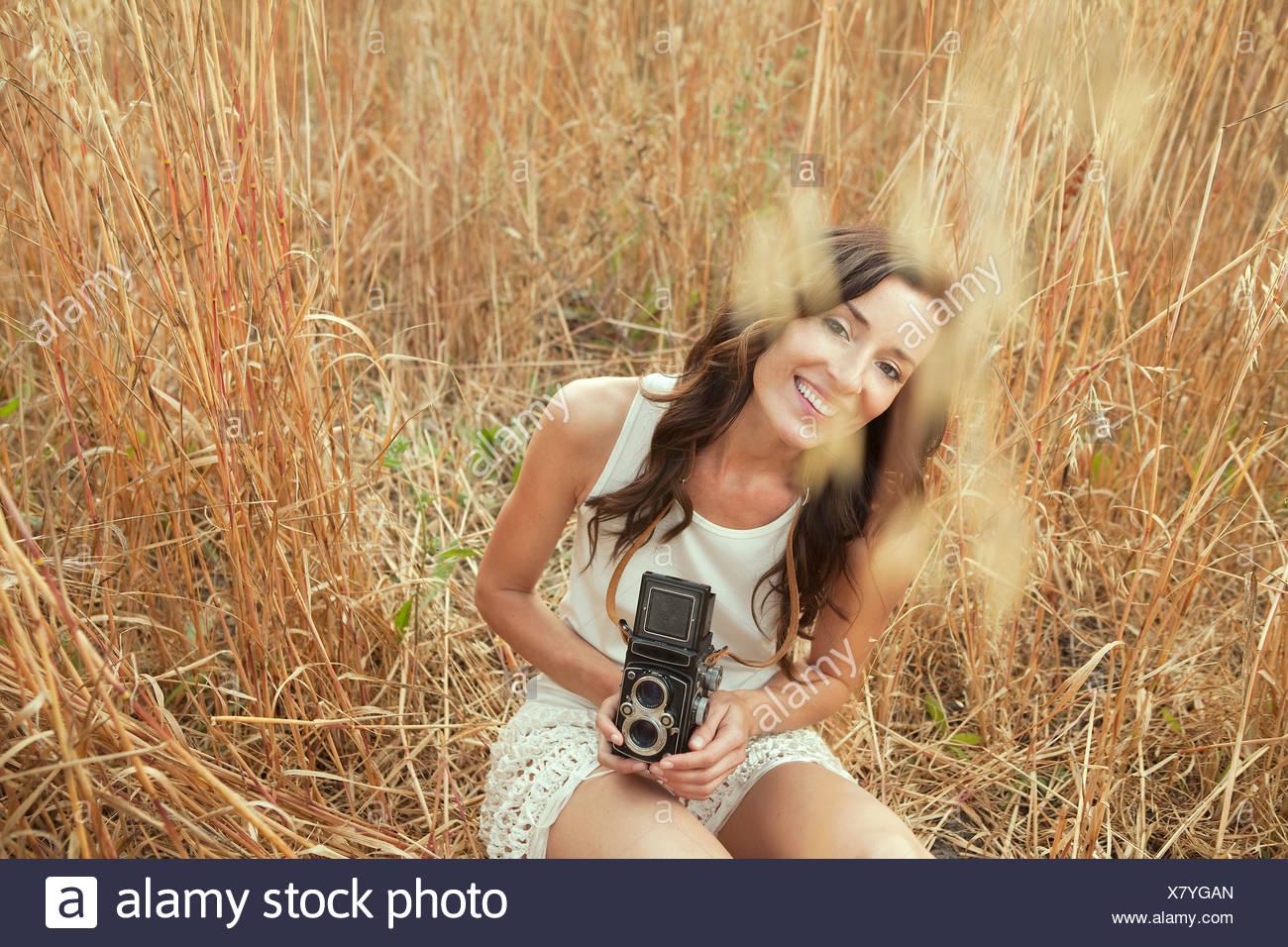 La mujer en el campo sujetando la cámara a la vieja usanza Imagen De Stock