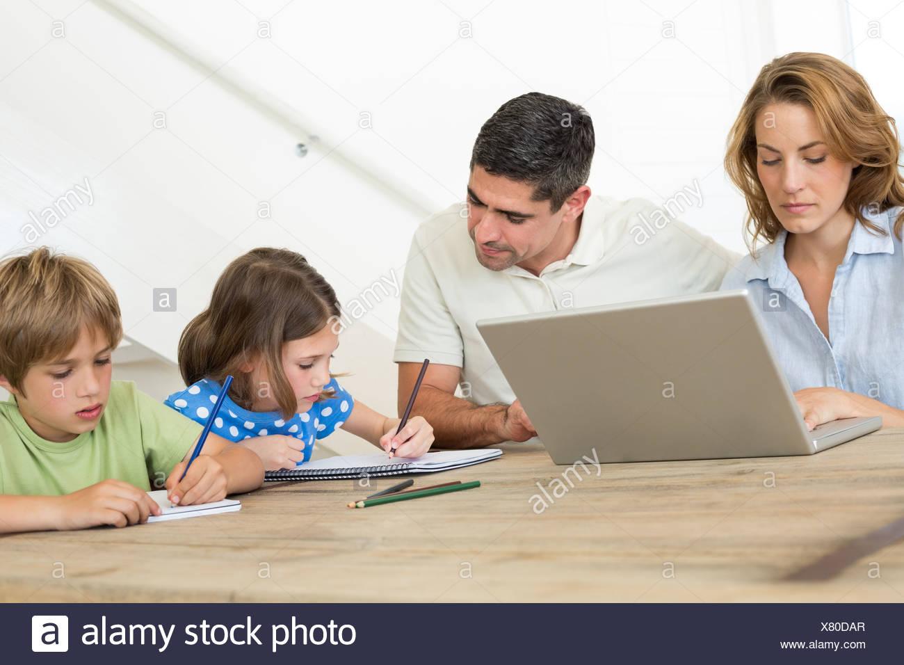 Madre utilizando el portátil mientras el padre ayuda a niños para ...