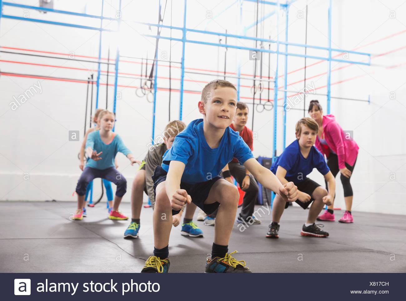 Los niños practican enojado gorilla walk en clase de Crossfit Imagen De Stock
