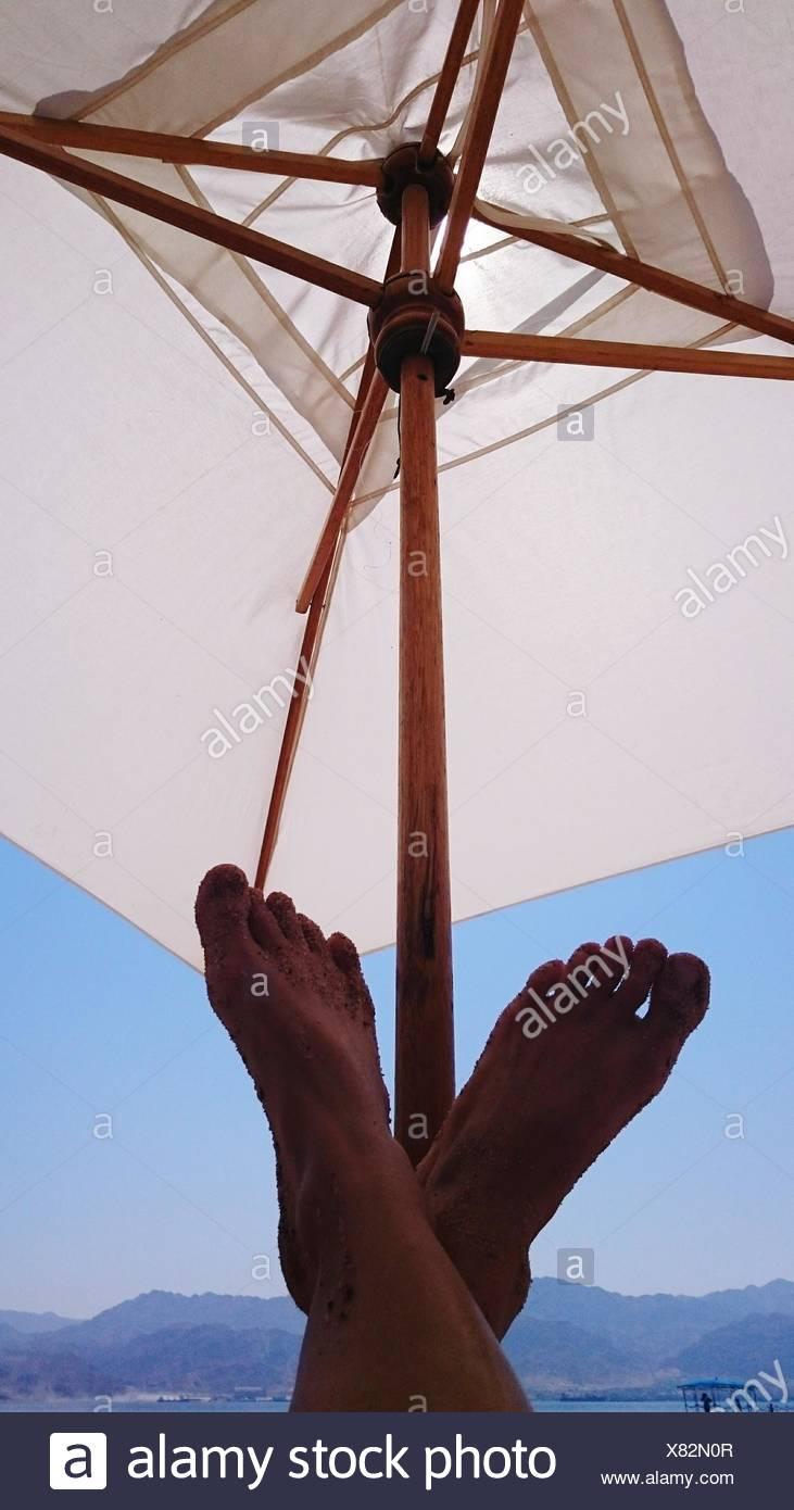 Bajo la sección de la persona contra la sombrilla Imagen De Stock