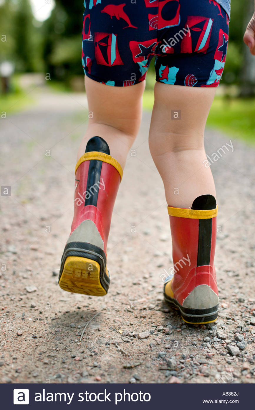 Suecia, Little Boy (2-3) caminando en botas de goma Imagen De Stock