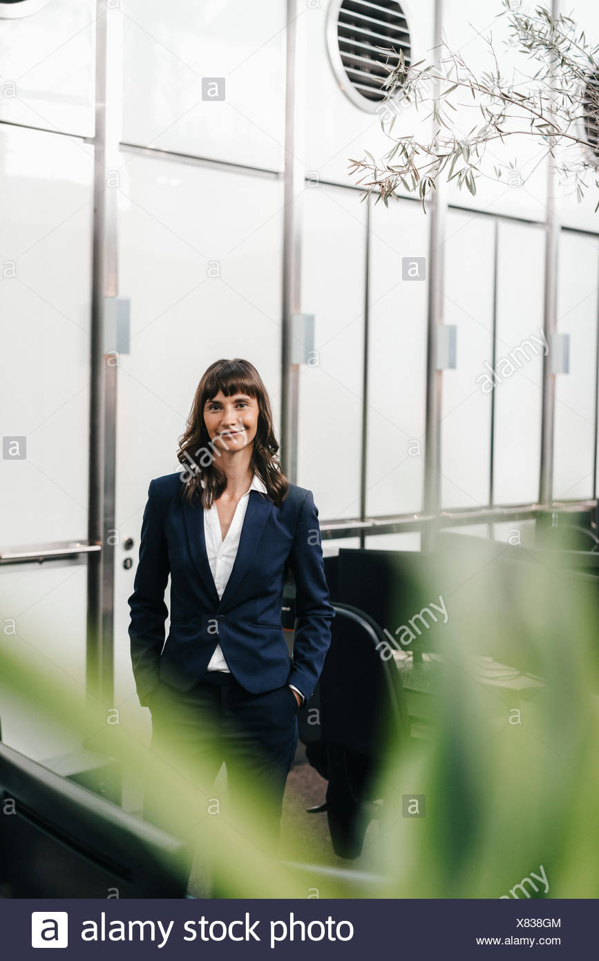 Exitosa empresaria de pie en la oficina con las manos en los bolsillos Imagen De Stock