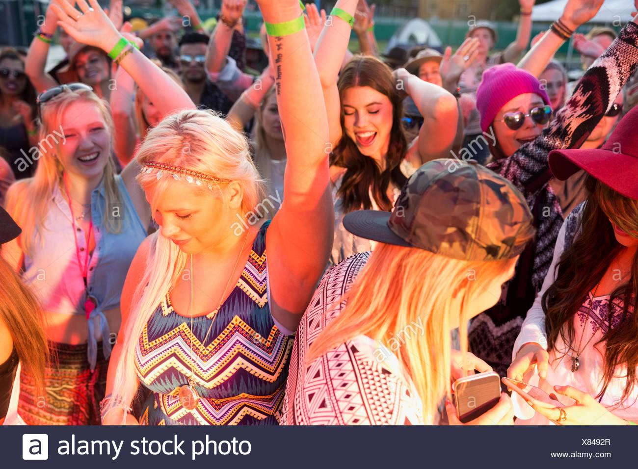 Las mujeres jóvenes bailando en multitud en el festival de música de resumen Imagen De Stock