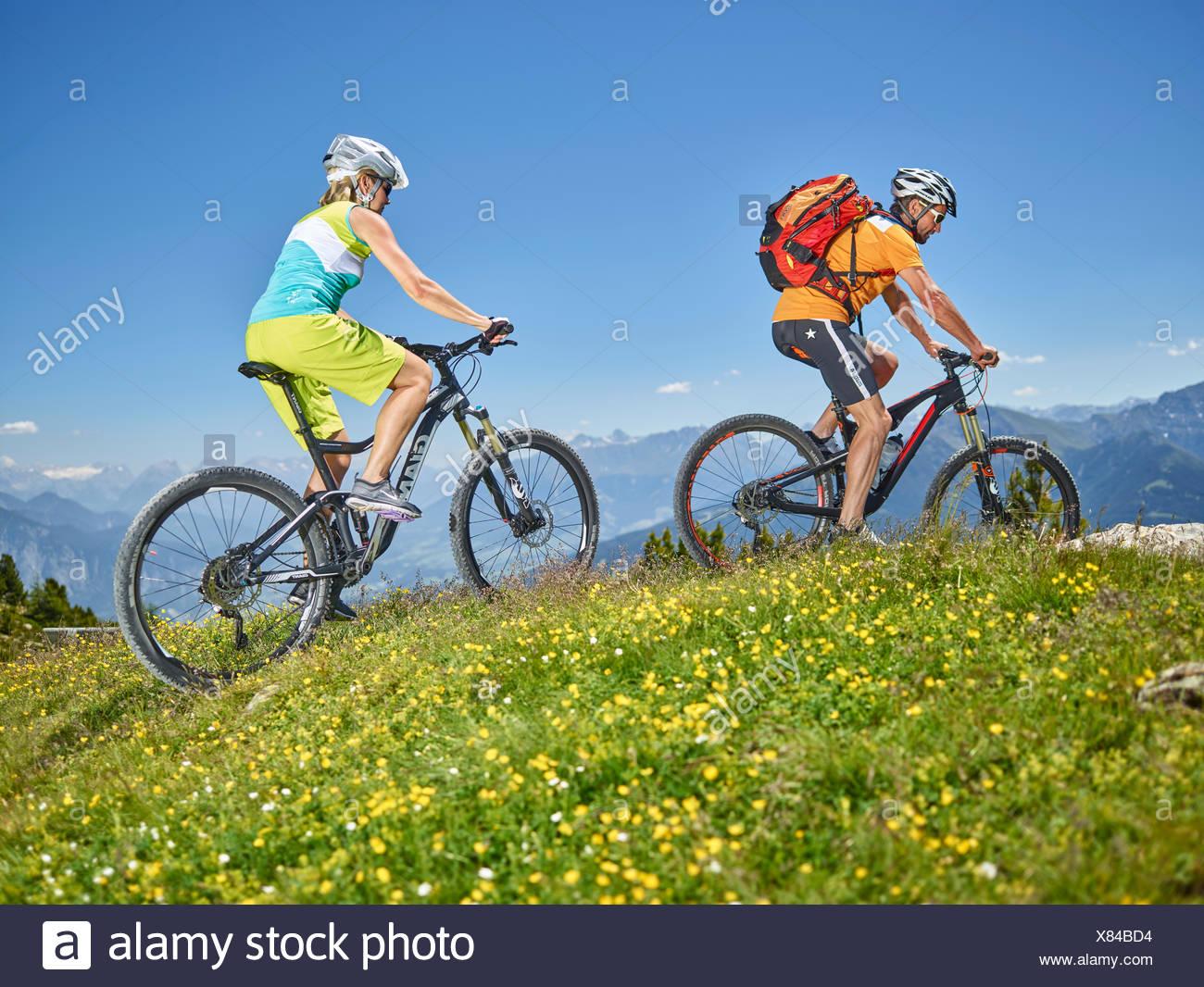 Hombre y mujer 40-45 AÑOS 35-40 años con los cascos de ciclo con sus bicicletas de montaña, Zirbenweg, Patscherkofel, Innsbruck, Tirol Foto de stock