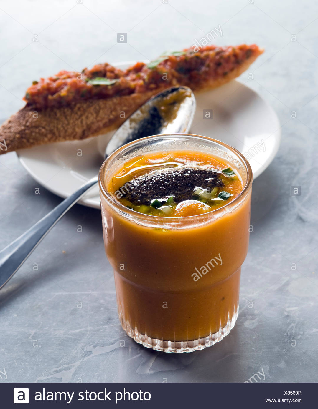 Gazpacho andaluz con una quenelle de aceitunas negras y bruschetta Imagen De Stock