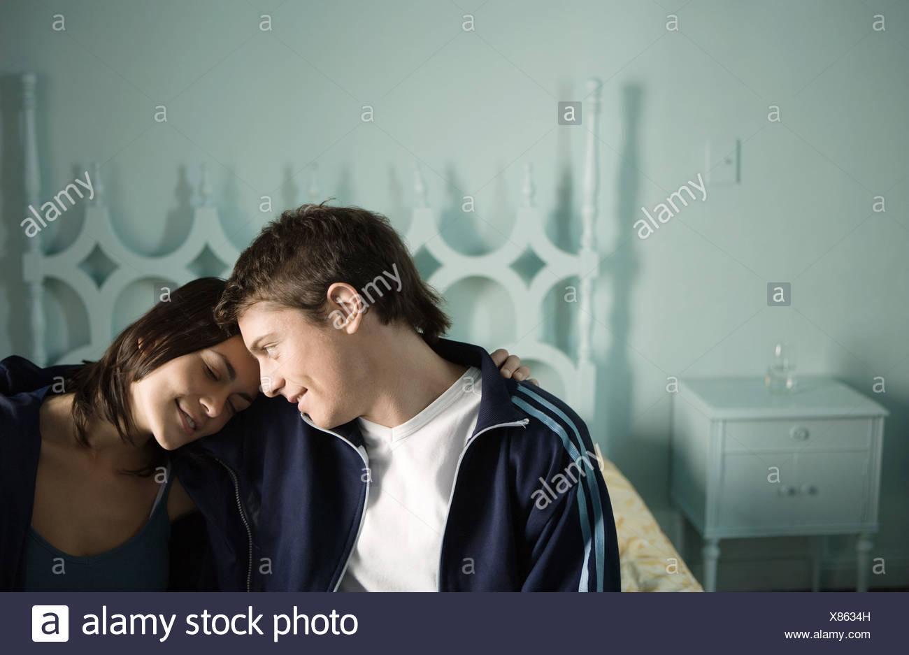 Pareja joven sentada en el borde de la cama con cabezas juntos Foto de stock