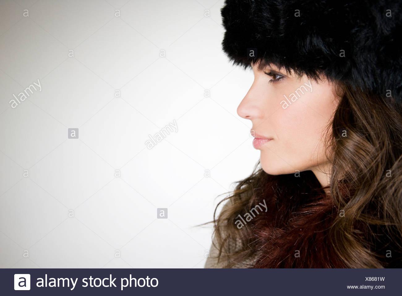 Una joven mujer vistiendo un sombrero de piel, sonriendo Imagen De Stock