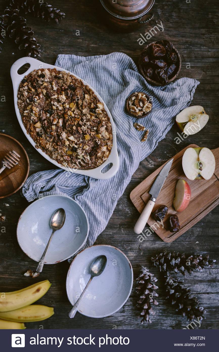 Avena cocida con manzanas, dátiles, plátano y nuez, que acaba de salir del horno, a punto de ser servido y mostrada en una reclama w Foto de stock
