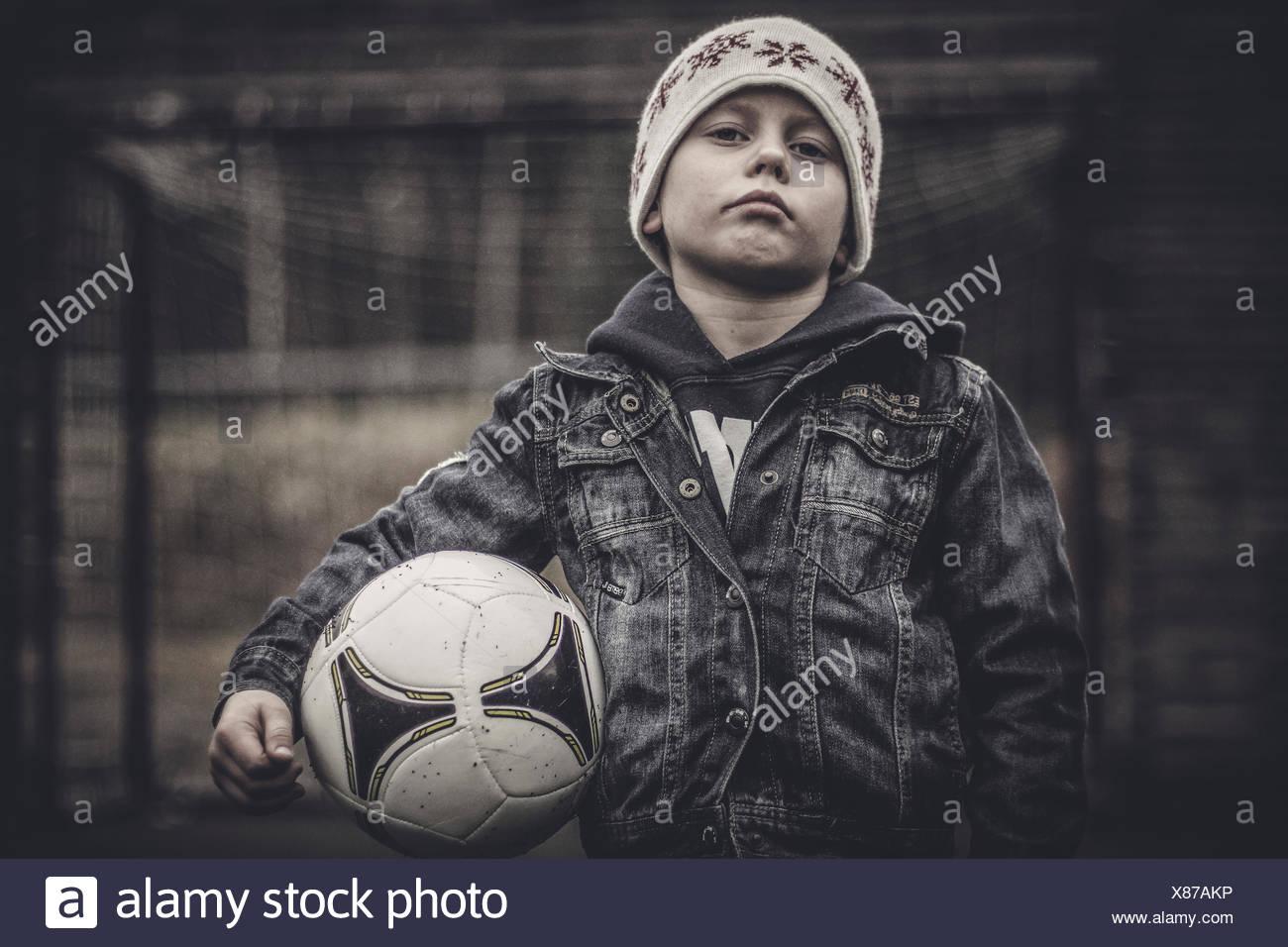 Retrato de una grave niño sosteniendo un balón de fútbol Imagen De Stock