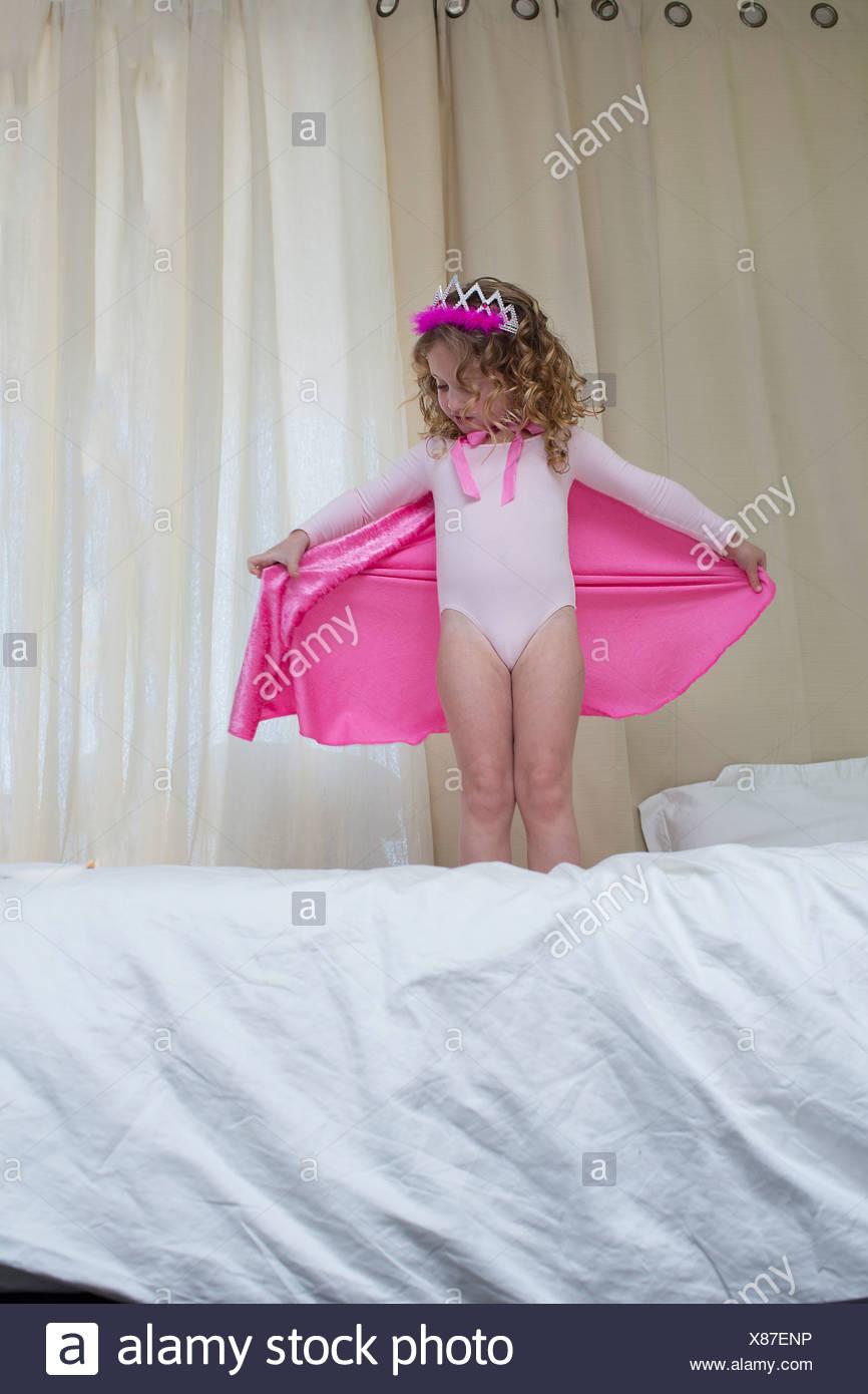 Niña vestida como una princesa de pie en la cama Imagen De Stock