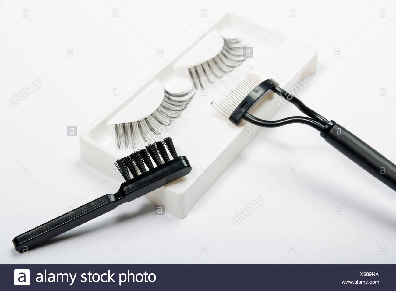 Fake pestañas, lash Peine y cepillo sobre fondo blanco, cerrar Foto de stock
