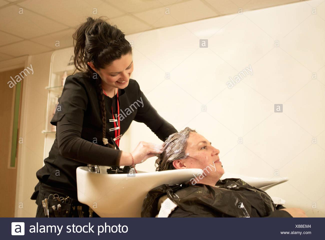 El estilista de cabello lavado clientes Foto de stock