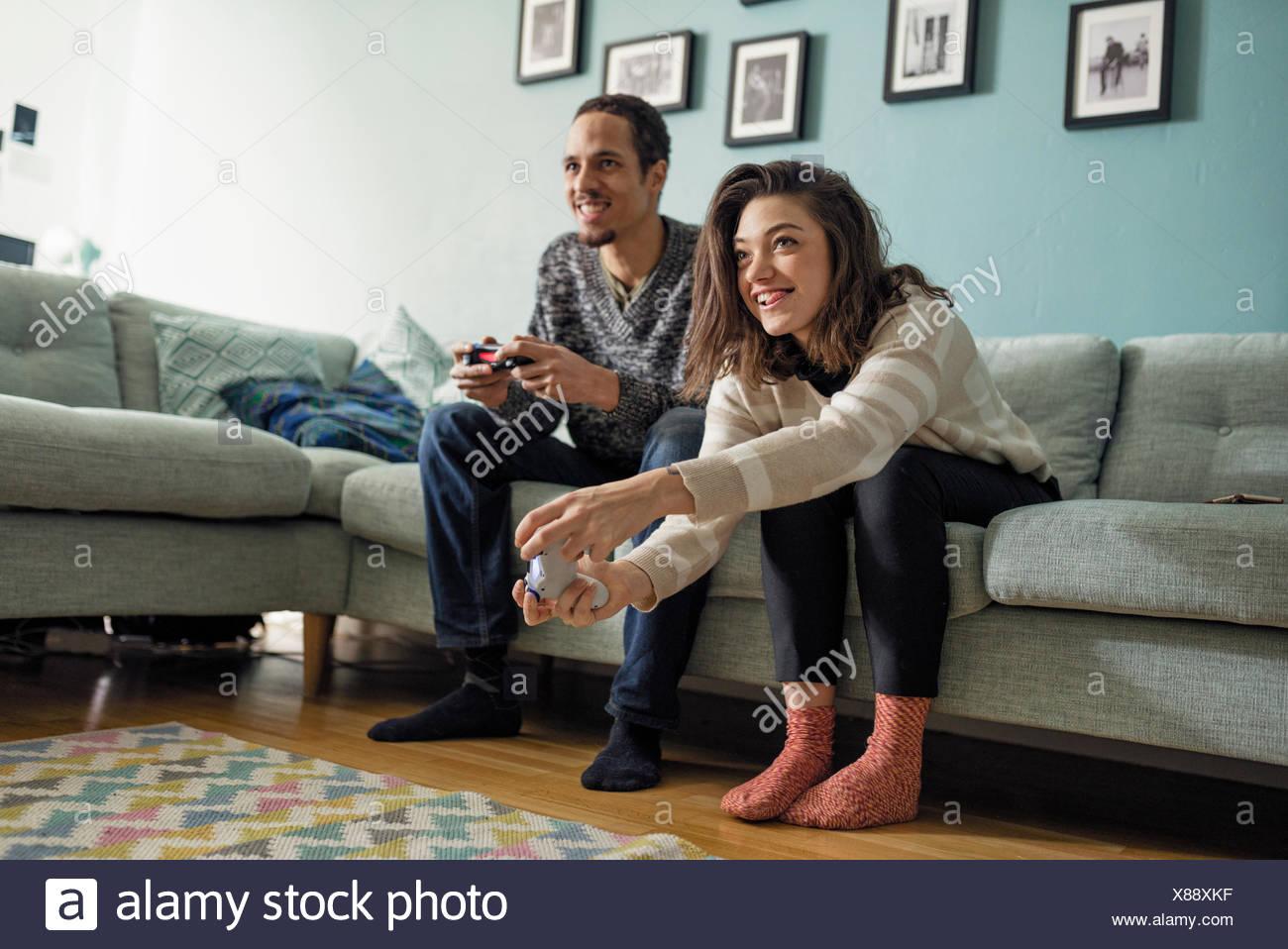 Suecia, pareja joven jugando juegos de video en la sala de estar Imagen De Stock