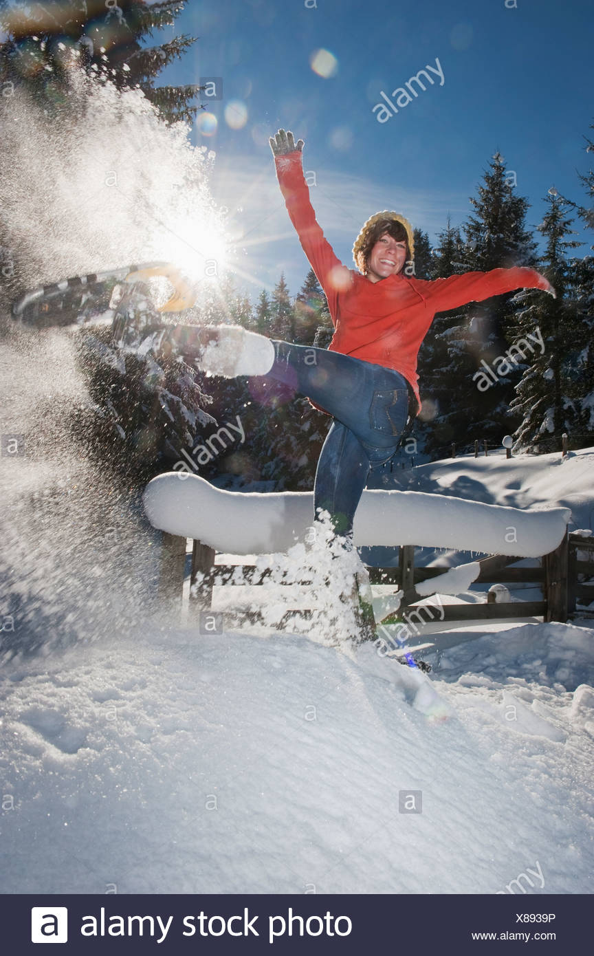 País Austria, Salzburgo, Flachau, joven mujer vistiendo zapatos de nieve saltando en la nieve Foto de stock