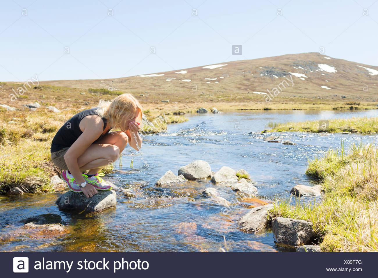 Suecia, Dalarna Grovelsjon, mujer de agua potable desde río de montaña Imagen De Stock