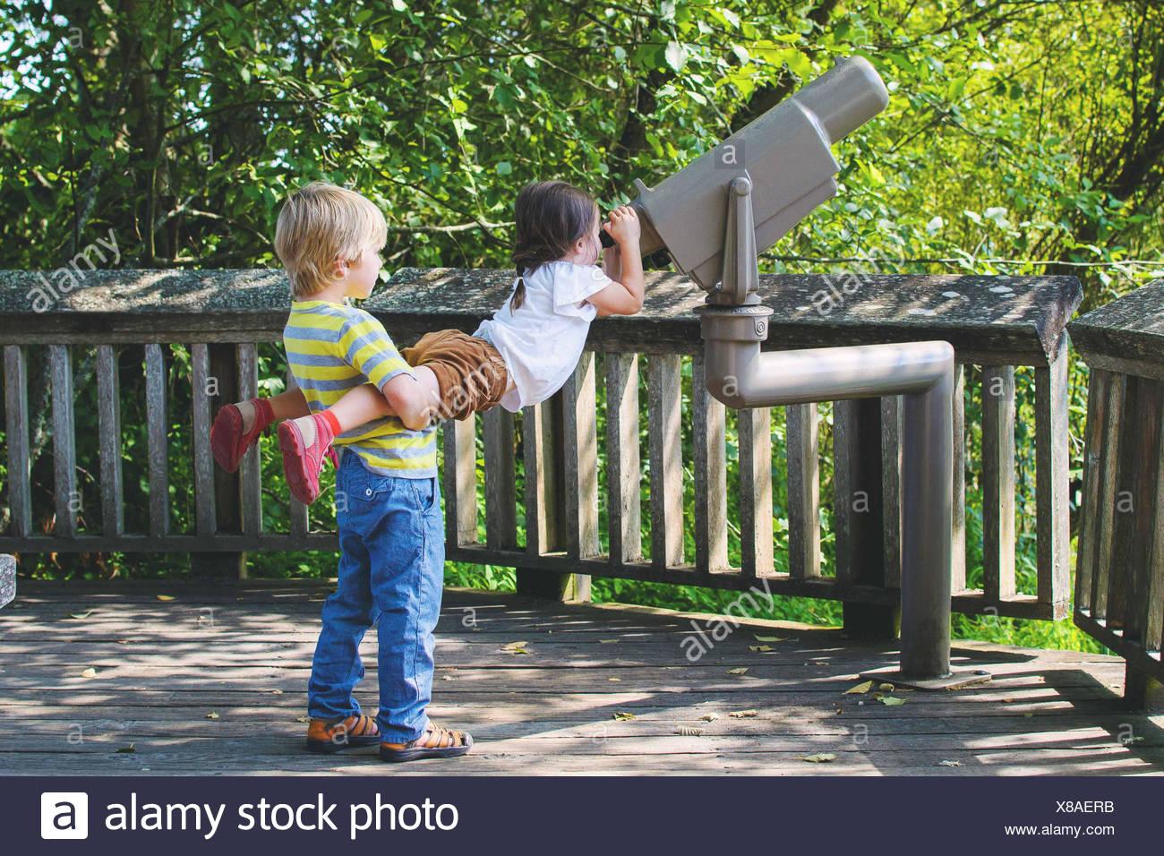 Chico Chica de elevación para mirar a través del telescopio Imagen De Stock
