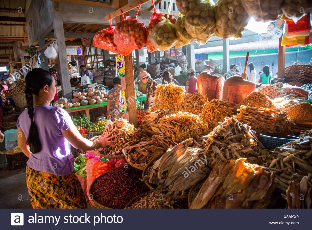Una mujer permanece junto a un proveedor cala llena con alimentos secos. Imagen De Stock