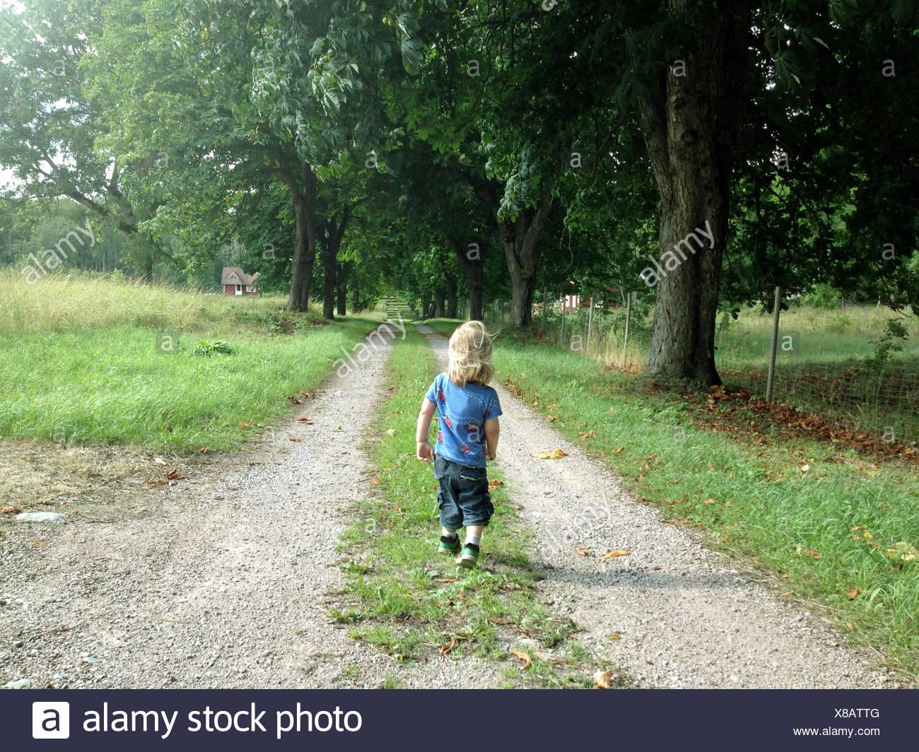 Muchacho caminando a lo largo de country road, Suecia Foto de stock