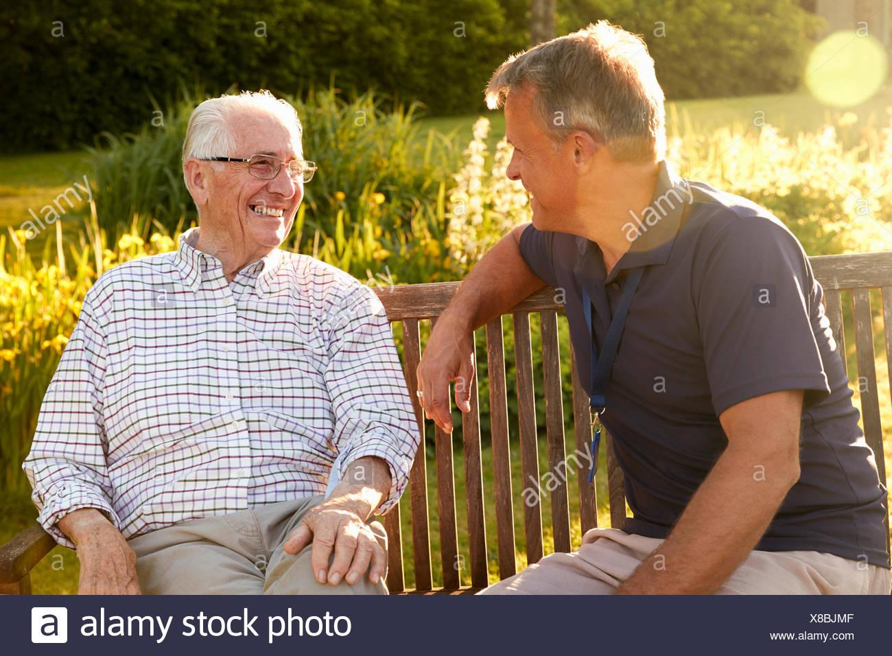 Hombre visitando altos pariente masculino en instalaciones de vida asistida Imagen De Stock