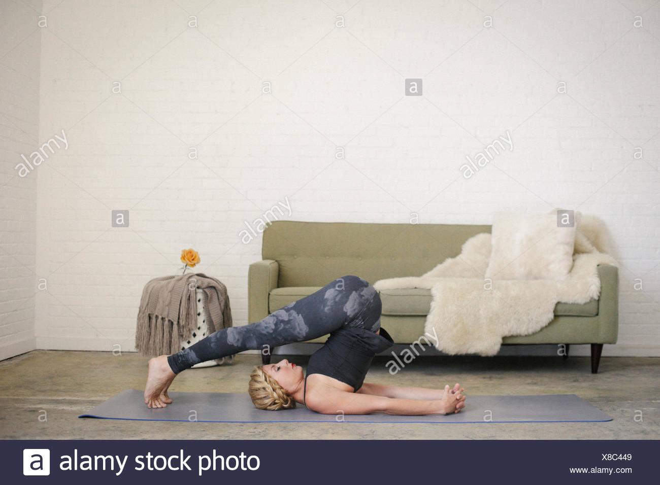 Una mujer rubia en un leotard negro y polainas, acostado sobre una estera del yoga en una habitación, hacer yoga, las piernas dobladas encima de su cabeza. Imagen De Stock