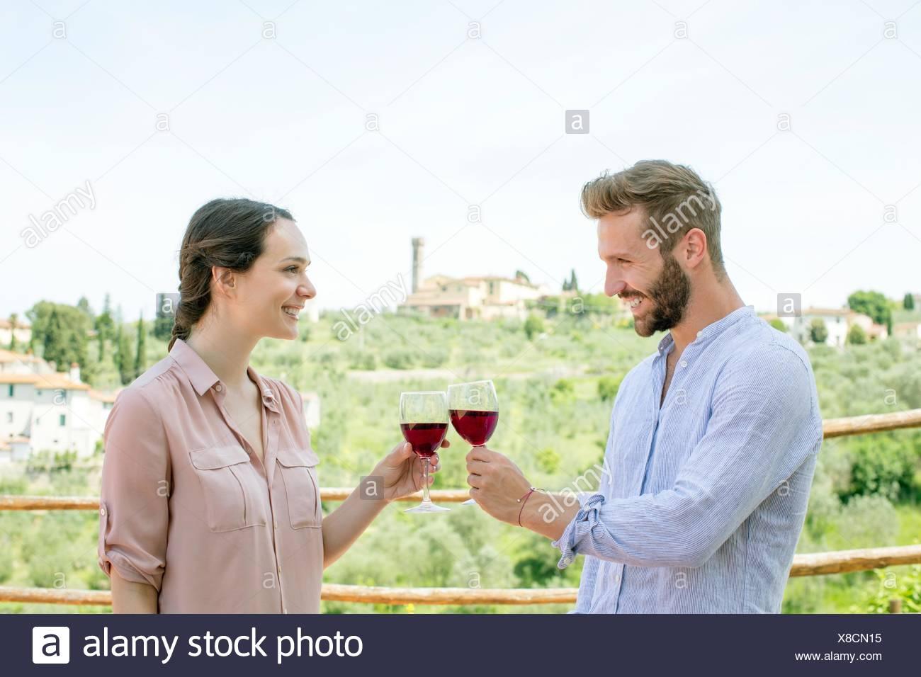 Cintura para arriba vista lateral de la joven pareja cara a cara haciendo un brindis sonriendo Imagen De Stock
