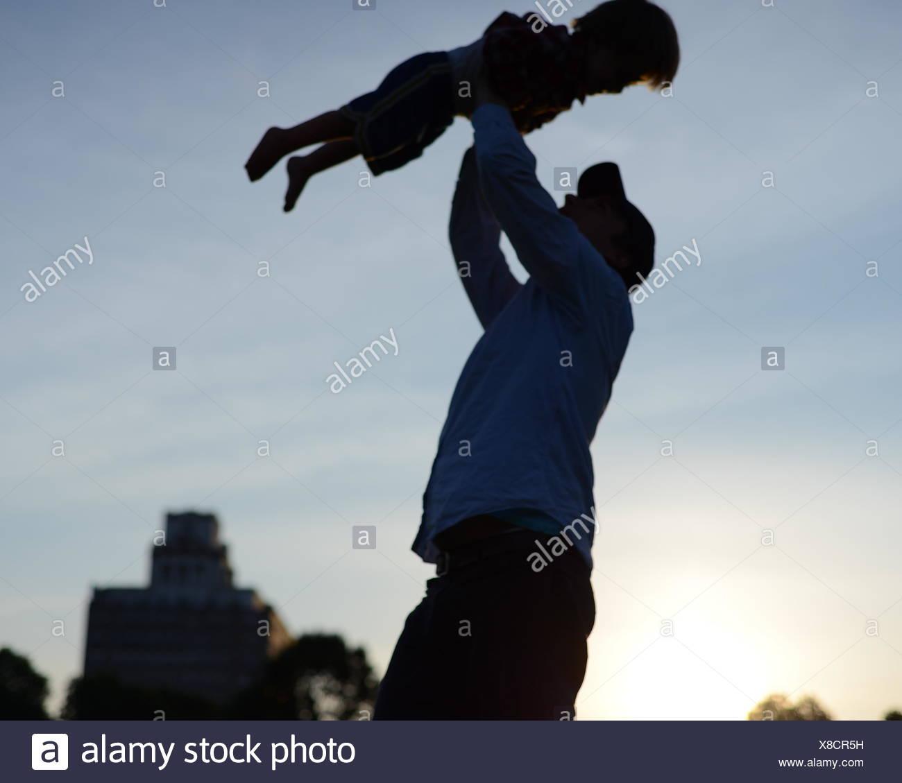 Ángulo de visión baja de hombre llevando bebé contra el cielo Imagen De Stock