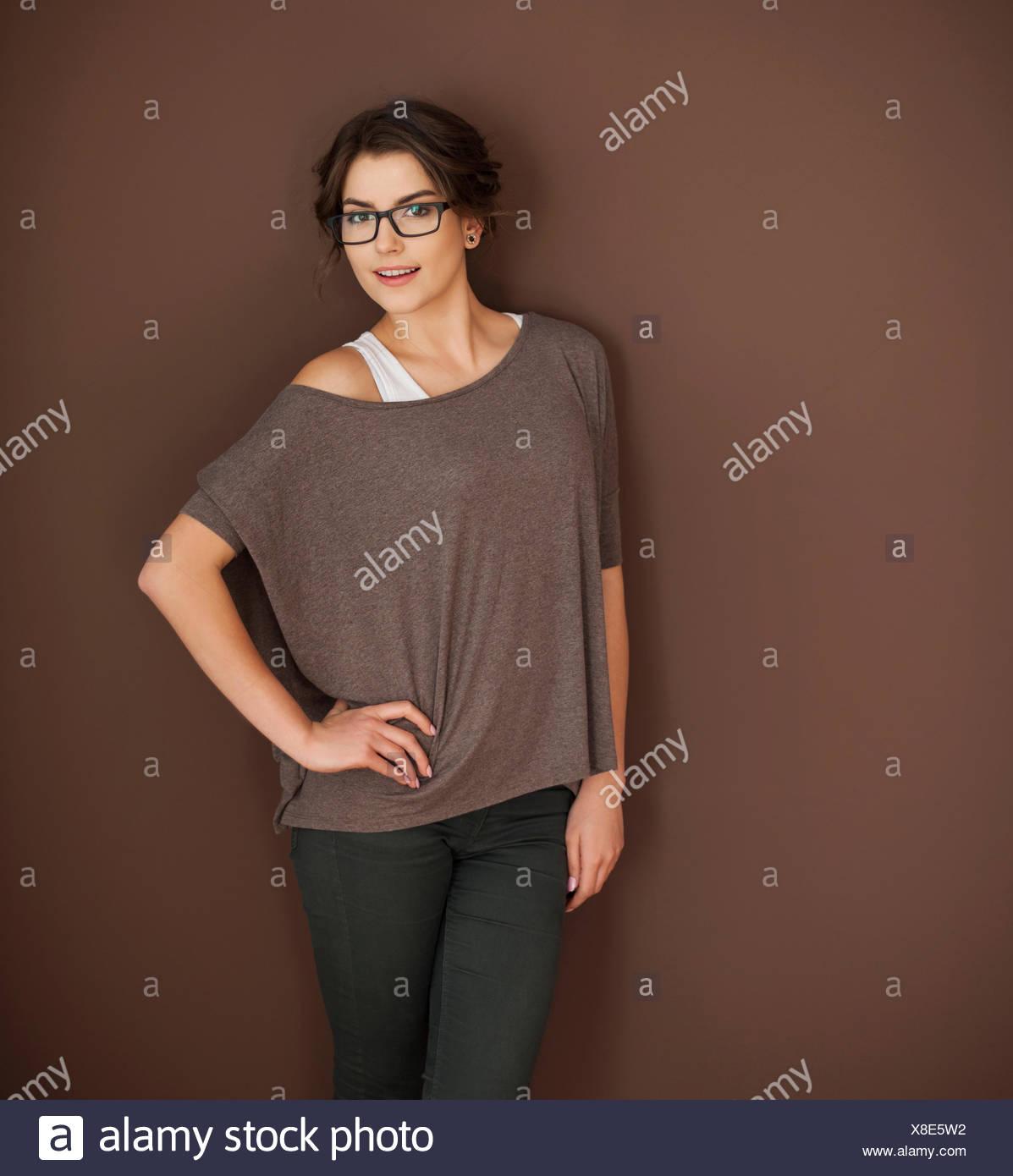 Hermosa mujer posando contra el fondo marrón Imagen De Stock