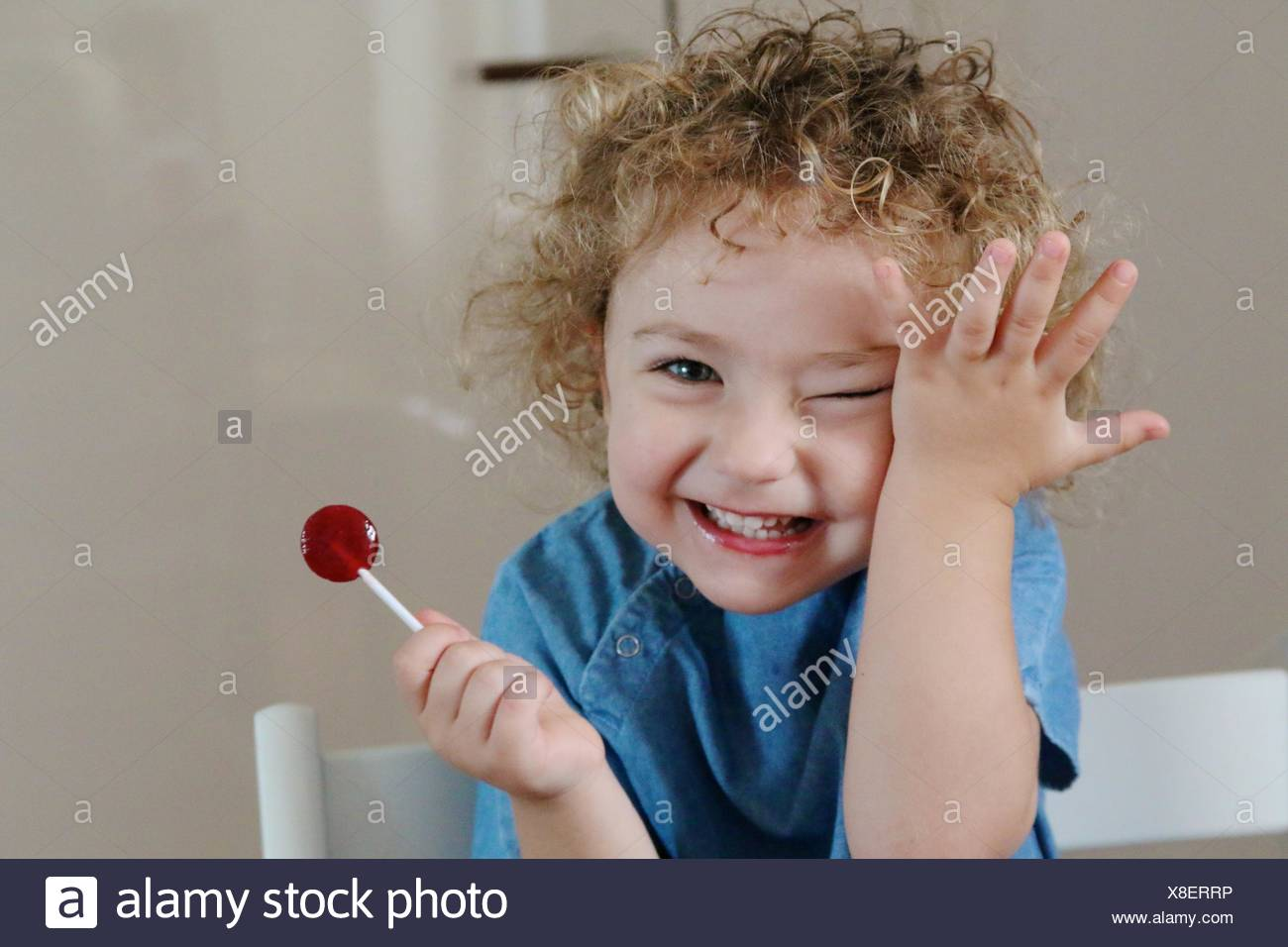 Chica (2-3) con piruleta sonriendo Imagen De Stock